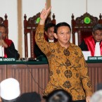 "Jakarta Gov. Basuki ""Ahok"" Tjahaja Purnama gestures to visitors inside a courtroom during his trial"