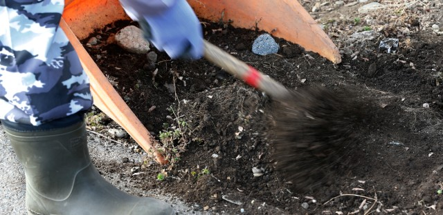 A worker removes the contaminated topsoil at a private house's garden in Minamisoma, Fukushima Prefecture, northeastern Japan on Feb. 4, 2016.