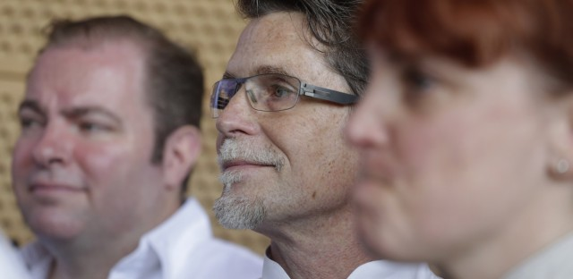 Chef Rick Bayless, center, listens with other top Chicago chefs during a news conference Tuesday, May 20, 2014, in Chicago. (AP Photo/M. Spencer Green)