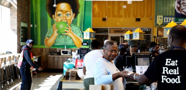 A mural in the Englewood Whole Foods shows a child biting into a bright green apple. Some residents say awareness of increased options for fresh produce hasn't reached the community in the way the store had envisioned. (Andrew Gill/WBEZ)
