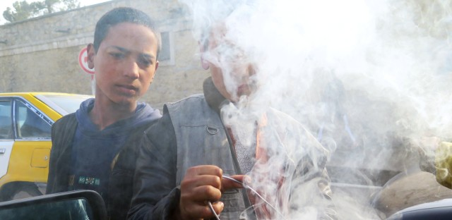 Young boys wave smoldering tin cans at cars in Kabul, Afghanistan. The smoke from the seeds inside the cans is believed to ward off evil.