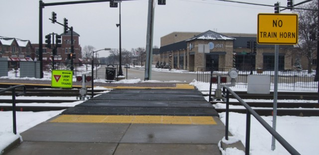 Signage at Metra's Bartlett station on the Milwaukee District/West Line route indicates safety precautions for pedestrians crossing the tracks.