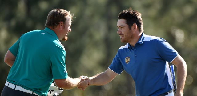 Louis Oosthuizen (right) shakes hands with his playing partner J.B. Holmes after the final round of the Masters on Sunday. Oosthuizen made an unlikely hole-in-one after his ball smacked Holmes' and then trickled into the cup. HARRY HOW / GETTY IMAGES