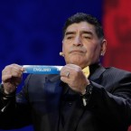 Argentine soccer legend Diego Maradona holds up the team name of England during the 2018 soccer World Cup draw in the Kremlin in Moscow, Friday, Dec. 1, 2017.