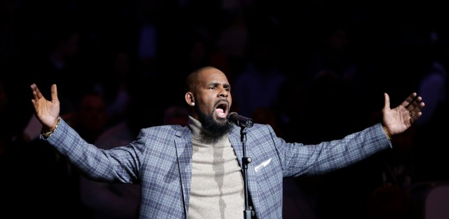 R. Kelly performs the national anthem before an NBA basketball game in New York on Nov. 17, 2015.