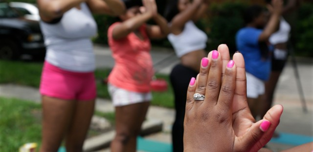 Tameka Lawson, executive director of local nonprofit I Grow Chicago, leads a yoga class along the often violent streets of Chicago's Englewood neighborhood on June 24, 2014.