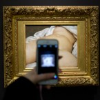 "In this Feb.12 2016 file photo, a visitor takes a picture of Gustave Courbet's 1866 ""The Origin of the World,"" at Musee d'Orsay museum, in Paris. A French teacher, whose Facebook account was suspended in 2011 after he posted a photo of a famous 19th-century nude painting, is suing Thursday Feb. 1, 2018 the California-based social network Facebook for alleged ""censorship"". Frederic Durand-Baissas, a 59-year-old Parisian teacher and art lover, posted a photo of ""The Origin of the World,"" which depicts female genitalia."