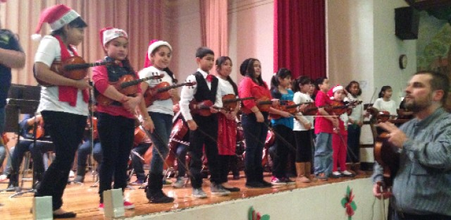 Music teacher Artus Weible prepares orchestra students for a performance at their holiday concert at Chopin Elementary.