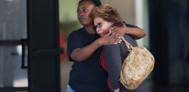 Two women embrace at a community center where family members have been gathering to pick up survivors after the shooting rampage at a social services center in San Bernardino, Calif.