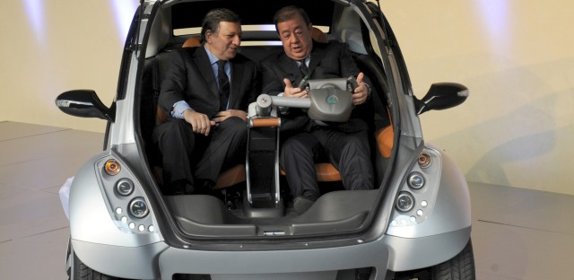 The then-president of the European Commission, Jose Manuel Barroso (left), and Jesus Echave, the Spanish chairman of a consortium of seven small Basque companies, sit together in a prototype of the Hiriko car, during a 2012 event in Brussels.