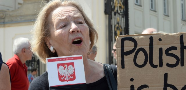 A woman holding a copy of Poland's constitution with a black ribbon shouts slogans in front of the presidential palace in Warsaw, Poland, Monday, July 24, 2017. Polish President Andrzej Duda announced that he will veto two contentious bills widely seen as assaults on the independence of the judicial system. (AP Photo/Alik Keplicz)