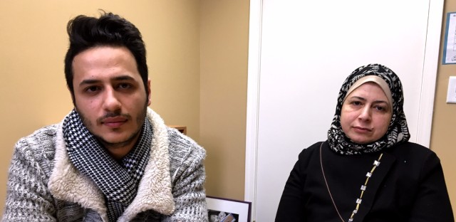 Bilal Rajoub (left) and Iman Kashkash talk about a relative still in a refugee camp in Jordan.