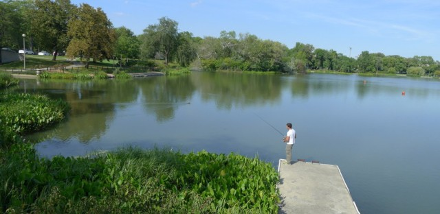 A man fishes in Humboldt Park lagoon in early fall.