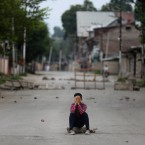 A protester covers his face as he sits on a rock during an anti-India protest in Srinagar, India, Friday, Aug. 9, 2019. The predominantly Muslim area has been under an unprecedented security lockdown and near-total communications blackout to prevent unrest and protests after India's Hindu nationalist-led government said Monday it was revoking Kashmir's special constitutional status and downgrading its statehood.