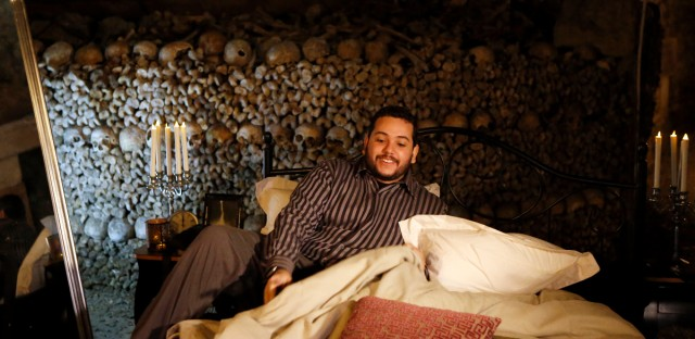 Guest Brazilian Pedro Arruda, 27, poses in the bed prior to spend the Halloween night with his mother Monica in Paris' creepy Catacombs amid skulls and bones, in Paris, France, Saturday, Oct, 31, 2015. House-sharing company Airbnb struck a spooky one-off deal with Paris' City Hall to sublet the subterranean ossuaries, the final resting place of 6 million bodies to the winner of a worldwide competition.