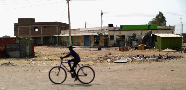 A child bikes along a main road in Bentiu. The town has been almost completely abandoned since the civil war began in 2013. Now some people are coming back, and pickup trucks serve as makeshift taxis.