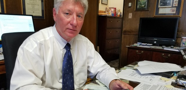 East Baton Rouge District Attorney Hillar Moore, who wants Apple or the FBI to unlock an iPhone 5s, has a stack of articles about encryption on his desk.
