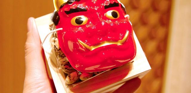 Mini oni demon mask with soybeans in wooden sake masu box at Mitsukoshi in Tokyo, Japan on Setsubun