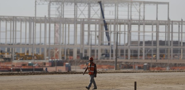A man walks past a nearly deserted construction site Wednesday in Villa de Reyes, San Luis Potosi, Mexico, as workers shut down operations and remove equipment from the site of a canceled $1.6 billion Ford plant. Ford's cancellation, which costs the region thousands of projected jobs, has sounded alarms in Mexico and sent its currency tumbling.