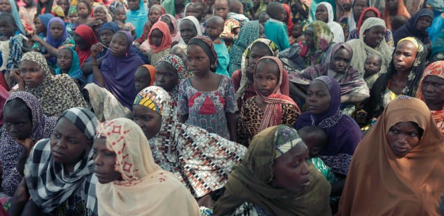 In this Tuesday, Dec. 8, 2015 file photo, women and children displaced by Boko Haram attacks are seen at Furore camp in Yola, Nigeria. First come the whispers, then accusations loud enough to raise alarms throughout villages ravaged by extremist violence. Next, people accused of being Boko Haram are rounded up, sometimes by the military, sometimes by a civilian self-defense force. Many are never seen again.