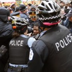 Chicago Police officers take a protester into custody during a scuffle at a police bicycle barricade on Chicago's Magnificent Mile Thursday, Dec. 24, 2015, in Chicago. The Christmas Eve Day protest calling for the resignation of Mayor Rahm Emanuel is the latest in a series of demonstrations in the city since the release last month of police video showing a white officer shoot a black teenager 16 times. (AP Photo/Charles Rex Arbogast)