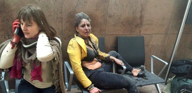 In this photo provided by Georgian Public Broadcaster and photographed by Ketevan Kardava two women wounded in Brussels Airport in Brussels, Belgium, after explosions were heard Tuesday, March 22, 2016. A developing situation left at least one person and possibly more dead in explosions that ripped through the departure hall at Brussels airport Tuesday, police said. All flights were canceled, arriving planes were being diverted and Belgium's terror alert level was raised to maximum, officials said.