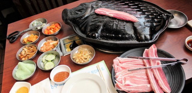 Korean tabletop barbecue with samgyeopsal (pork belly sliced thick and thin) plus banchan (small side dishes) at Jang Choong Dong restaurant in the village of Niles, in the new Koreatown area in the north suburbs of Chicago.
