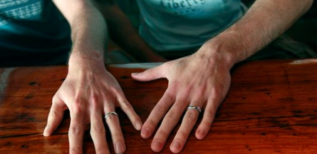 David Peters, right, and Luke Whited, an Illinois couple joined in civil union, show their rings in a New Orleans gay bar after President Obama's statement of support of gay marriage Wednesday.