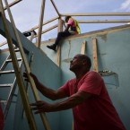 In this Nov. 15, 2017 photo, Pedro Deschamps helps workers hired by FEMA to carry out the installation of a temporary awning roof at his house, which suffered damage during Hurricane Maria, in San Juan, Puerto Rico.