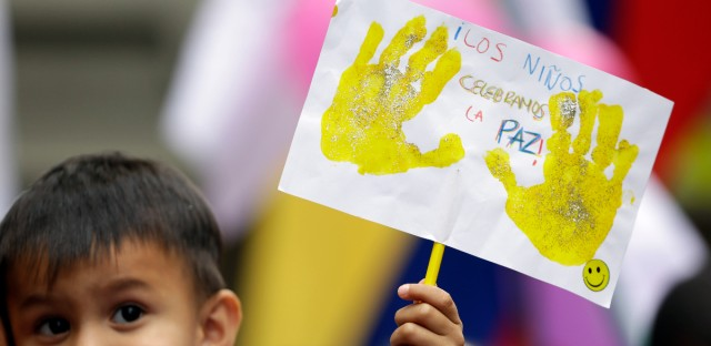 "A boy holds a sign that reads in Spanish ""Children celebrate peace"" during the celebration of the agreement between Revolutionary Armed Forces of Colombia, FARC, and Colombia's government, in Bogota, Colombia last week. Colombian President Juan Manuel Santos and the head of the country's leftist FARC rebels agreed Thursday on a cease-fire and rebel disarmament deal that moves the country closer to ending a 52-year war that has left more than 220,000 people dead."