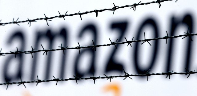 The Amazon logo is seen behind barbed wire at the company's logistic center in Rheinberg,Germany. The European Union is telling member state Luxembourg to get $295 million in back taxes from Amazon in Brussels' latest regulatory move targeting U.S. tech companies accused of tax avoidance, it was reported on Wednesday, Oct. 4, 2017.