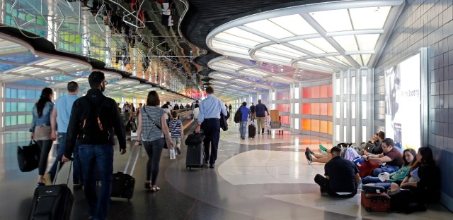 Travelers walk down the walkway between terminals at O'Hare International Airport, Monday, May 30, 2016, in Chicago.