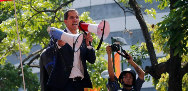 Venezuela's self-proclaimed president Juan Guaido speaks to supporters as he calls for the military to rise up and oust President Nicolas Maduro in Altamira Plaza in Caracas, Venezuela, Tuesday, April 30, 2019. Guaido and jailed opposition leader Leopoldo Lopez took to the streets with a small contingent of heavily armed troops early Tuesday in a bold and risky call for the military to rise up and oust Maduro.