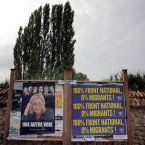 An electoral board showing France's far-right National Front president Marine Le Pen and reading: 100% National Front. 0% migrants is pictured during a demonstration in Forges-les-Bains, south of Paris, France, Saturday, Oct. 8, 2016. French villagers are protesting the arrival of migrants who are being spread out around the country as the government shuts down the slum-like camp in Calais that has become a flashpoint in Europe's migrant crisis.