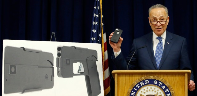 Standing beside photographs of a new product, U.S. Sen Charles Schumer, (D-New York), shown holding an iPhone 5S, voices his opposition to a handgun that appears to be a cell phone during a news conference in his office, Monday, April 4, 2016, in New York. According to the website of Ideal Conceal, the company has developed a double-barreled, .380 caliber handgun that can serve as a concealed weapon. The gun lists for $395. (AP Photo/Kathy Willens)