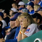 A Cubs fan holds her head in her hands at Wrigley Field during Game 4 of the World Series