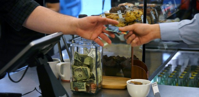 A customer gives their credit card to a cashier at a Chicago coffee shop on June 7.