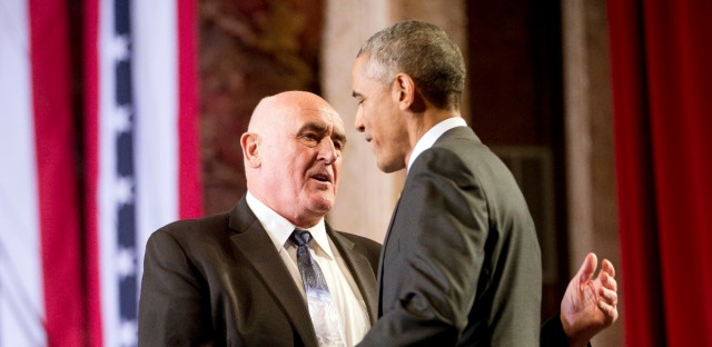 President Barack Obama, right, is introduced by Billy Lawless, left, on stage before speaking at the Copernicus Community Center in Chicago to discuss immigration reform, Tuesday, Nov. 25, 2014. Obama visited his hometown to promote his executive action on immigration.