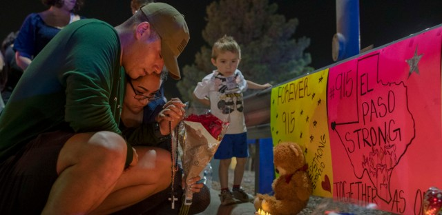 Rene Aguilar and Jackie Flores pray at a makeshift memorial for the victims of Saturday's mass shooting at a shopping complex in El Paso, Texas, Sunday, Aug. 4, 2019.