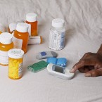 In this Monday, July 13, 2015 photo Earl Charles Williams Sr., 59, sits next to some of the medication he must take for his diabetes in his Chicago home. Williams was uninsured for about a year before a county-run clinic helped him sign up for care under the Affordable Care Act. More than a dozen states that opted to expand Medicaid under the Affordable Care Act have seen enrollments surge way beyond projections, raising concerns that the added costs will strain their budgets when federal aid is scaled back starting in two years.