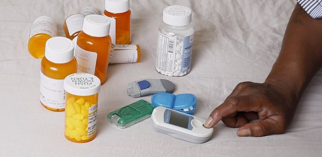 Earl Charles Williams Sr., 59, sits next to some of the medication he must take for his diabetes in his Chicago home in July of last year. Williams was uninsured for about a year before a county-run clinic helped him sign up for care under the Affordable Care Act. The lack of state budget in Illinois could become a problem for those insured by Medicaid if combined with policy proposed by President-elect Donald Trump.