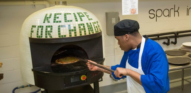 "Inmate Marcus Clay pulls pizza from an oven at the Cook County Jail in Chicago. Inmates in the jail's medium-security Division 11 are now allowed to order pizzas made by participants in the jail's ""Recipe for Change"" program, which teaches inmates about cooking and nutrition."