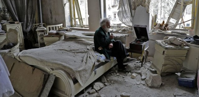 Mohammed Mohiedin Anis, or Abu Omar, 70, smokes his pipe as he sits in his destroyed bedroom listening to music on his vinyl player, gramophone, in Aleppo's formerly rebel-held al-Shaar neighbourhood.