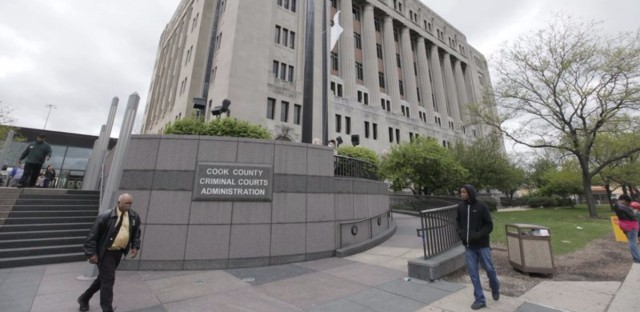People walk past the Cook County Criminal Courts Building in April 2012. Public Defender Amy Campanelli wants sheriff's deputies to monitor the lockup areas to prevent men in custody from exposing themselves to female attorneys. (M. Spencer Green/AP)