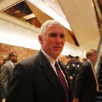 Vice President-elect Mike Pence, who is now overseeing President-elect Donald Trump's transition, walks by reporters while exiting Trump Tower on Tuesday.