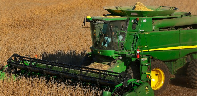 In this Tuesday, Oct. 21, 2014 photo, a central Illinois farmer uses a combine to harvest his soybean field in Loami, Ill.
