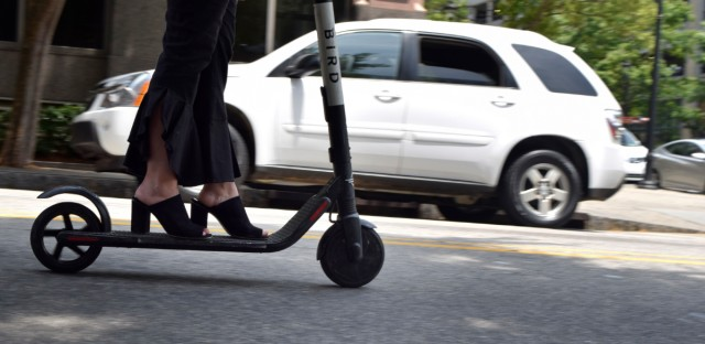 In this May 28, 2019, photo, a woman rides an electronic scooter in downtown Raleigh, N.C. Chicago is launching a pilot program with 2,500 electric scooters on June 15.