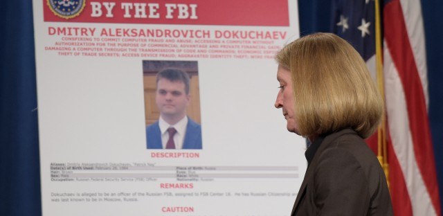 "Acting Assistant Attorney General Mary McCord walks past a ""FBI Wanted"" poster following a news conference at the Justice Department in Washington, Wednesday, March 15, 2017. The Justice Department announced charges against four defendants, including two officers of Russian security services, for a mega data breach at Yahoo."