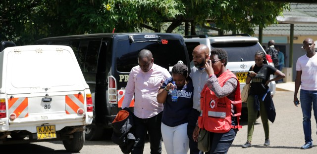 A unidentified relative is helped by a Red Cross worker after visiting the morgue in Nairobi, Kenya Thursday, Jan. 17, 2019. Extremists stormed a luxury hotel complex in Kenya's capital on Tuesday, setting off thunderous explosions and gunning down people at cafe tables in an attack claimed by Africa's deadliest Islamic militant group al-Shabab