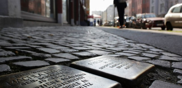 """People walking in Berlin, Germany, pass Stolpersteine, or """"stumbling stones,"""" which were created to remember victims of the Holocaust. A group of advocates in Chicago want to create similar public art for victims of the city's 1919 race riots."""